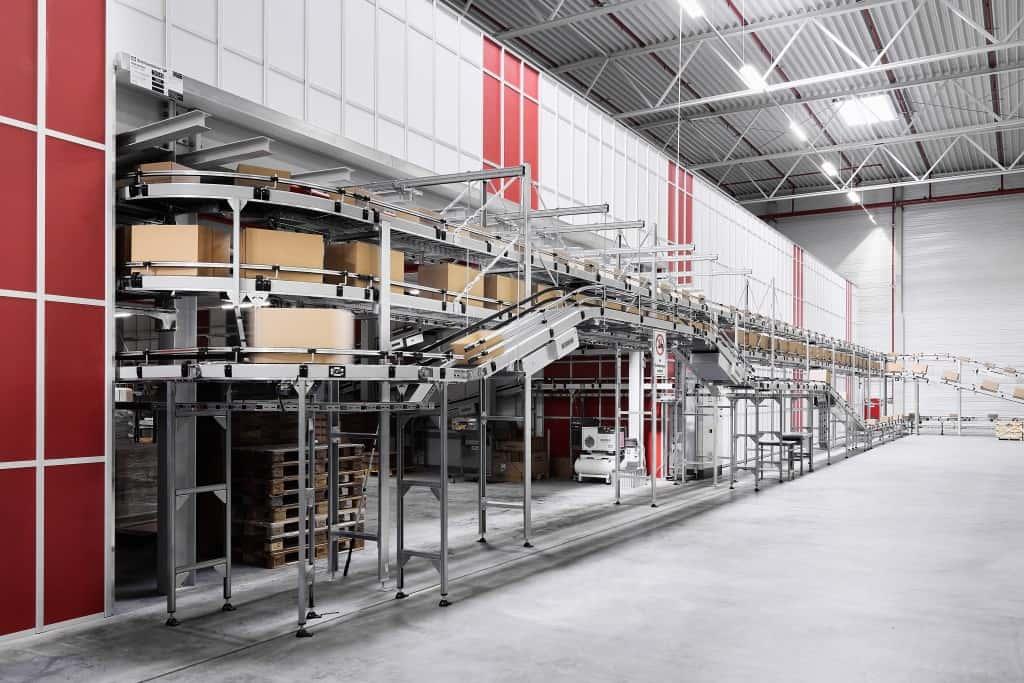 Förderbänder transportieren Kartons an die Arbeitsplätze im Inneren des AutoStore-Tunnels und wieder zurück.