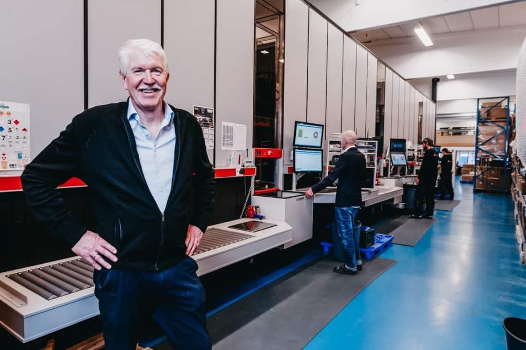 Algemeen directeur, Jan Kleven, glimlacht trots naar de camera voor de Elotecs AutoStore-oplossing met arbeiders die de havens op de achtergrond bedienen.